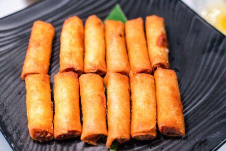 Fried Asian spring rolls with shrimps, vegetables, fruit...on buffet table Banco de Imagens