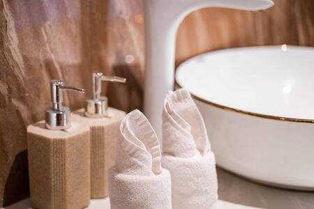 Modern hotel bathroom with towel, Liquid soap, shampoo bottle, wash bowl and faucet