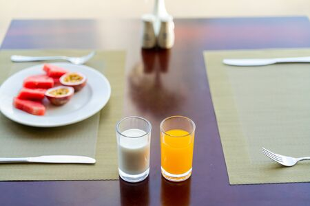 Fresh romantic breakfast table next to window with desert foods: fruits, juice and milk