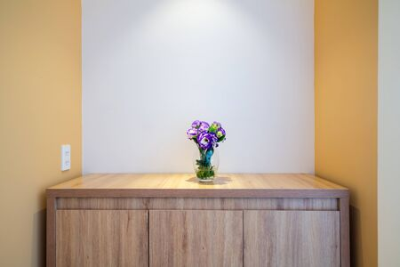 Flower in a glass vase on wooden table in hotel room Stock Photo