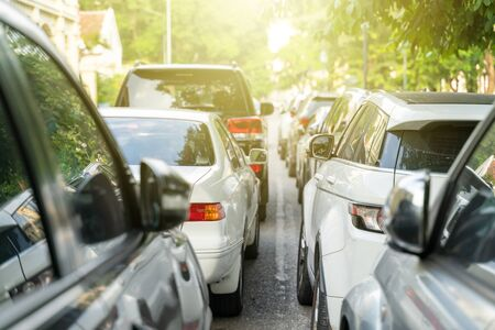 Long line of cars on urban street with rear view