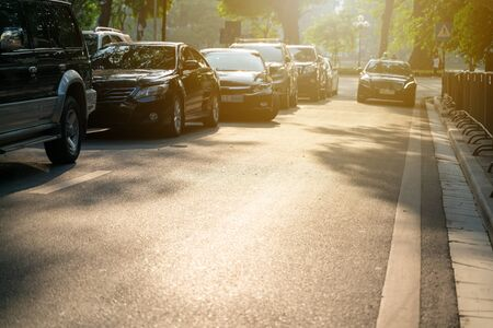 Copy space street with cars parking on urban street under brilliant sunlight