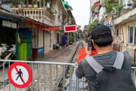 Male tourist taking photo of Hanoi railway next to the