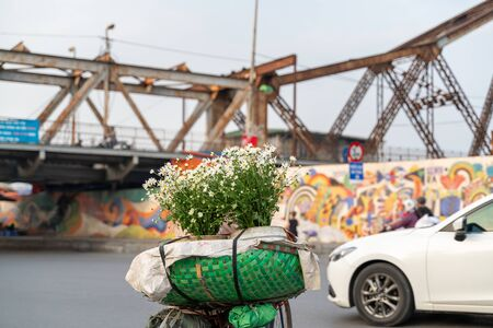 Flower vendor on Hanoi street at early morning with Long Bien old metal bridge on background