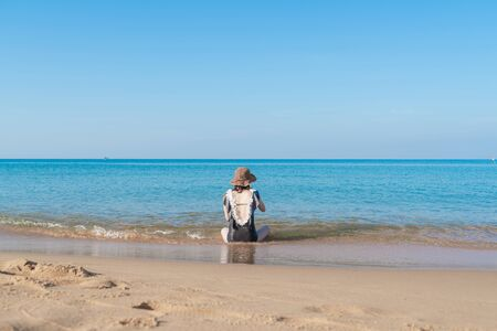 Tropical sea beach with young girl relaxing on sand Imagens