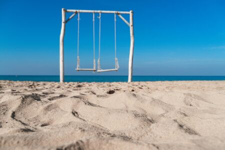 Empty swing on tropical beach with blue sky