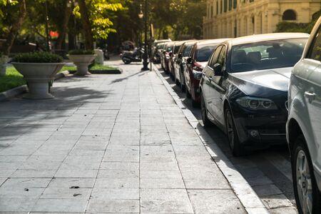 Voitures de stationnement parallèles sur rue urbaine. Stationnement extérieur sur route