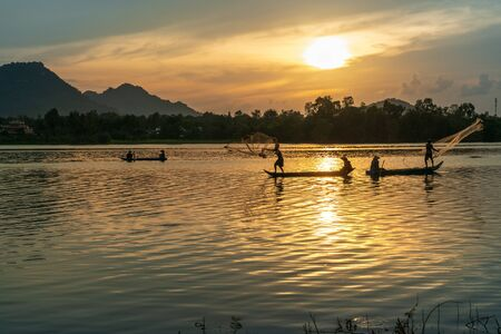Fisher men fishing on a fishing boat in river in Mekong Delta on floating water season at sunset