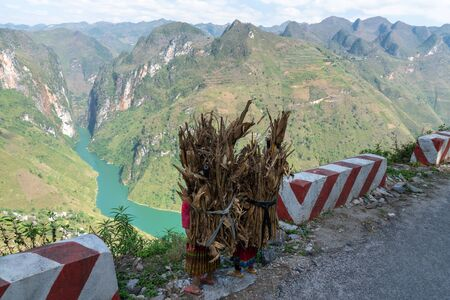 Ha Giang mountain view at Ma Pi Leng pass with children carry wood on back heading home on road