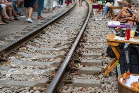 Railway cafe. People drink coffee or walking on railways waiting for train to arrive on railway road in Hanoi, Vietnam. Soft focus on the rails Banque d'images