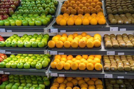 Fresh healthy fruits on shelves in supermarket