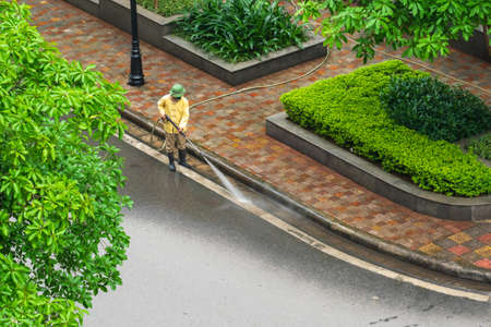 Aerial view of park with worker cleaning dirty street with high pressure cleaner