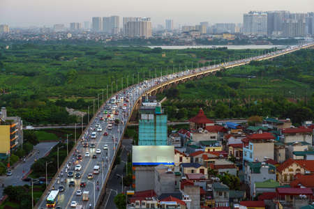 Cityscape of Hanoi skyline at Vinh Tuy bridge over Red river during sunset time
