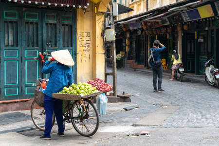 The street vendor with bike loaded of tropical fruits in old town street in Hanoi, old houses and street activites on background Banque d'images