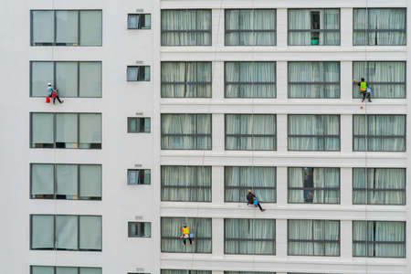 Asian industrial worker cleaning windows of a modern building.