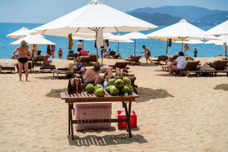 Coconut on the table on the beach in Nha Trang, Vietnam. Tourists enjoying the sun on background Stock Photo