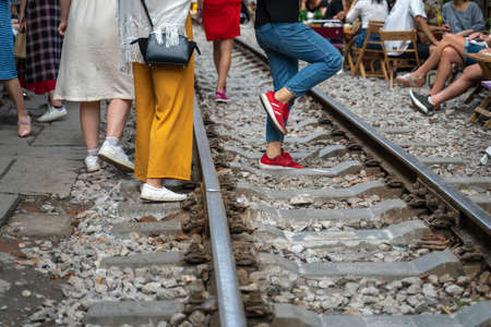 Railway cafe. People drink coffee or walking on railways waiting for train to arrive on railway road in Hanoi, Vietnam. Stock Photo