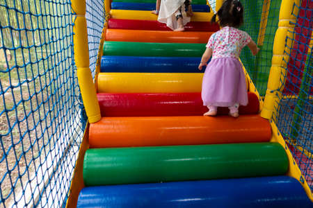 Colorful stairs in children play house, with child legs climbing up closeup