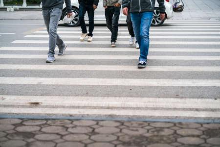 People walking across a street in Hanoi, Vietnam. Closeup