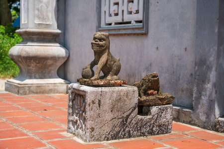 Old stone dog lion statue named Nghe in Vietnam ancient temple.