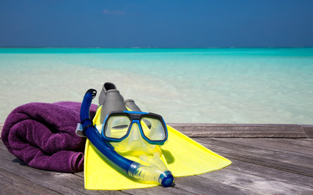 Mask, fins and towel lying on a jetty Stock Photo
