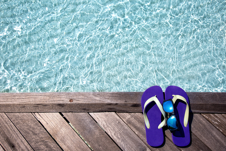 flops: Flip Flops and sunglasses on wodden jetty