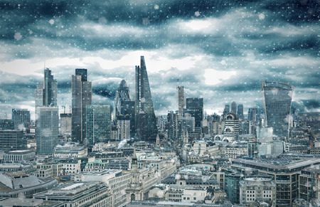The skyline of the City of London with a snow blizzard in winter, United Kingdom