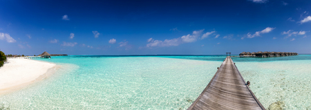 Panorama of an island in the Maldives with a white beach, turquoise waters and a wooden jetty Standard-Bild