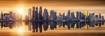 The modern skyline of Doha, Qatar, at sunset with reflections in the water Stock Photo