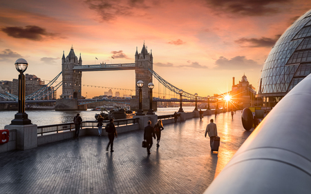 The Tower Bridge in London during sunrise and people rushing to their work Editorial