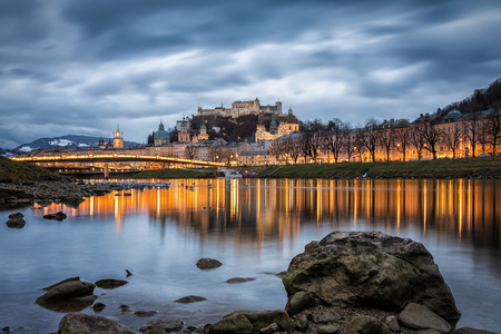 View from the river Salzach to the illuminated city of Salzburg in Austria during a cold winter evening