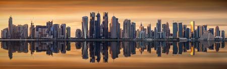 The modern skyline of Doha, Qatar, during a cloudy sunset