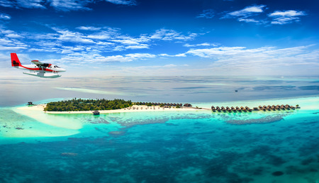 Aerial view of a seaplane approaching a tropical island in the Maldives