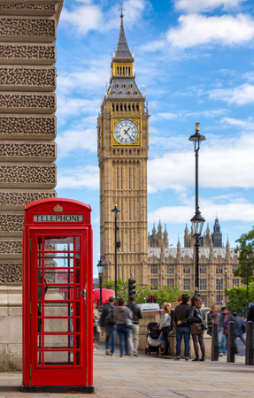 Red telephone booth in front of the Big Ben in London, United Kingdom, during a summery day