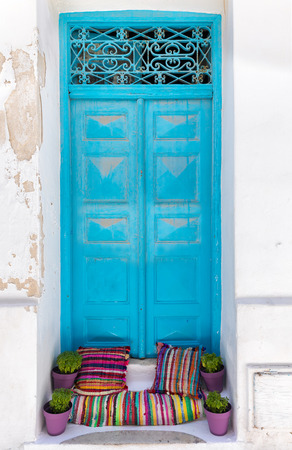 Classic blue door with colorful pillows on white house in the Cyclades of Greece Stock Photo