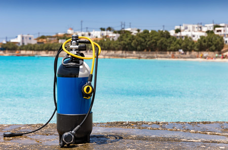 Scuba tank with regulator standing in front of turquoise waters Stock Photo