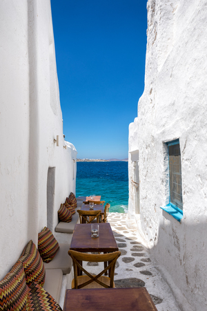 Benches and tables in a small, narrow alley facing the sea in Mykonos town, Greece Banco de Imagens