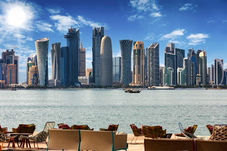 The skyline of Doha, Qatar with chairs and tables in front