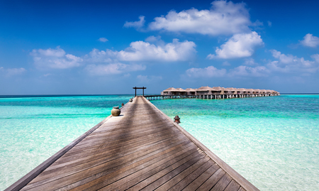Beautiful classic Maldives background with a wooden boardwalk and bungalows