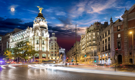 Gran Via street in Madrid after sunset with blurred traffic lights and full moon rising Stock Photo