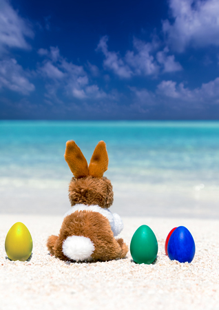 Easter bunny on colored easter eggs on a tropical beach Stock Photo