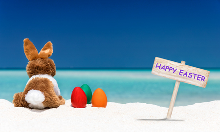 Bunny, easter eggs and Happy Easter sign on a tropical beach in the Maldives