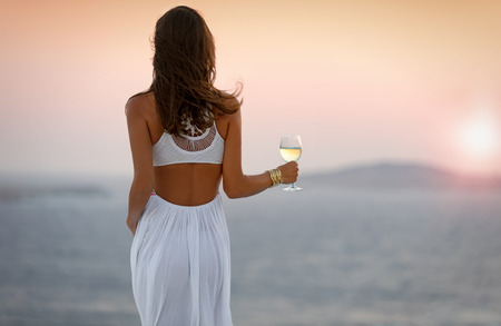 Woman is enjoying the sunset with a glass of wine Stock Photo