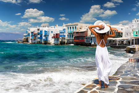 Attractive female tourist with white dress is overlooking famous Little Venice on Mykonos island, Greece Stock Photo