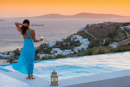 Attractive woman in blue dress enjoys the sunset at the pool Stockfoto