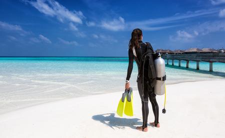 Female scuba diver with diving equipment on the beach at the Maldives Foto de archivo