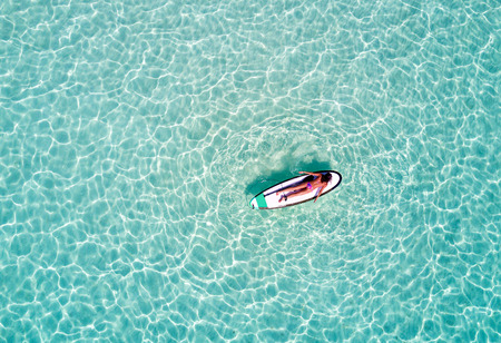 Aerial picture of a woman on a surfboard in turquoise waters in the Maldives