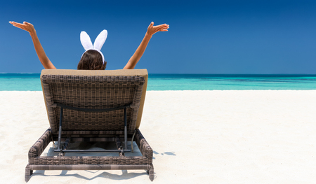 Woman with bunny ears on sunbed at the Maldives Stock Photo