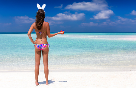 Woman with bunny ears and easter eggs on tropical beach
