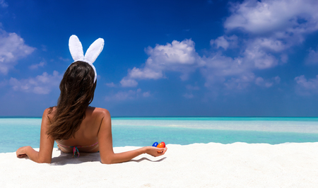 Woman with bunny ears and colorful easter eggs on a tropical beach in the Maldives Stockfoto